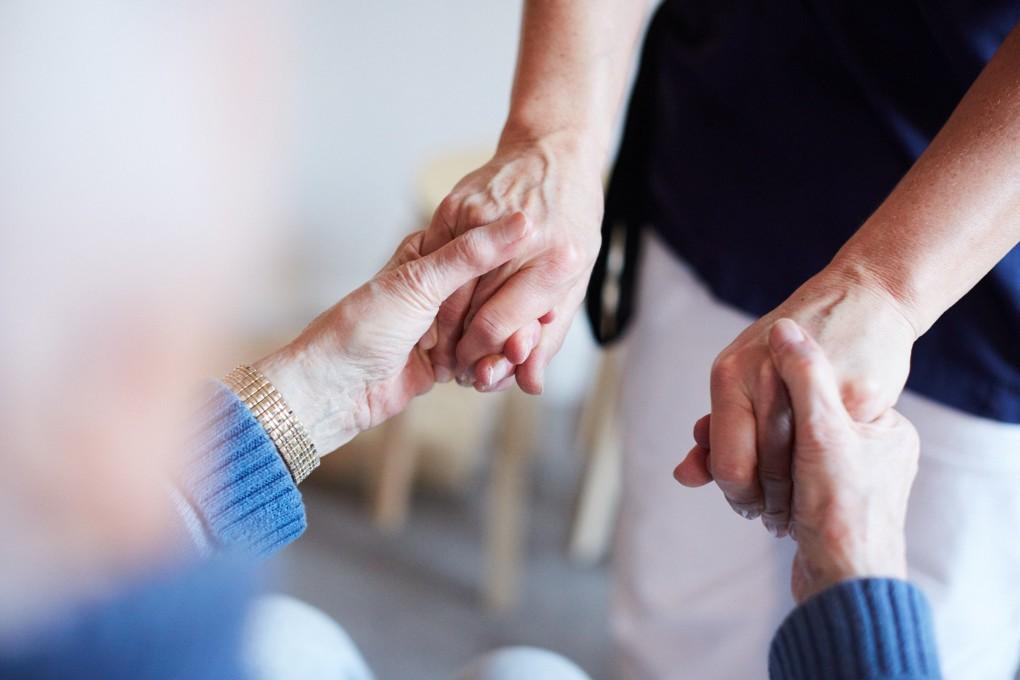 En sköterska håller en äldre patient i händerna. Fotograferat åt Praktikertjänst bildbank utav Paulina Westerlind