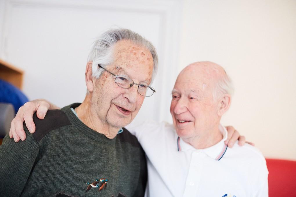 Två gym killar på över 90 år håller om varandra efter ett gympass på Kassernhöjden i Karlstad. Fotograferat av Paulina Westerlind åt Praktikertjänts bildbank