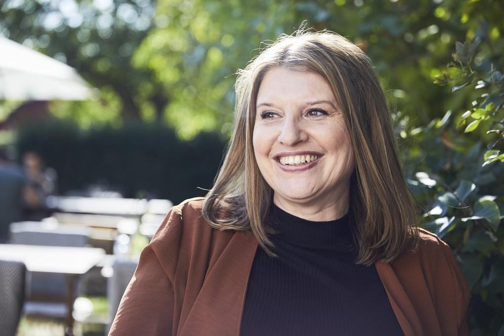 Författarporträtt av Simona Ahrnstedt med ett finurligt leende. Fotograferat av Paulina Westerlind