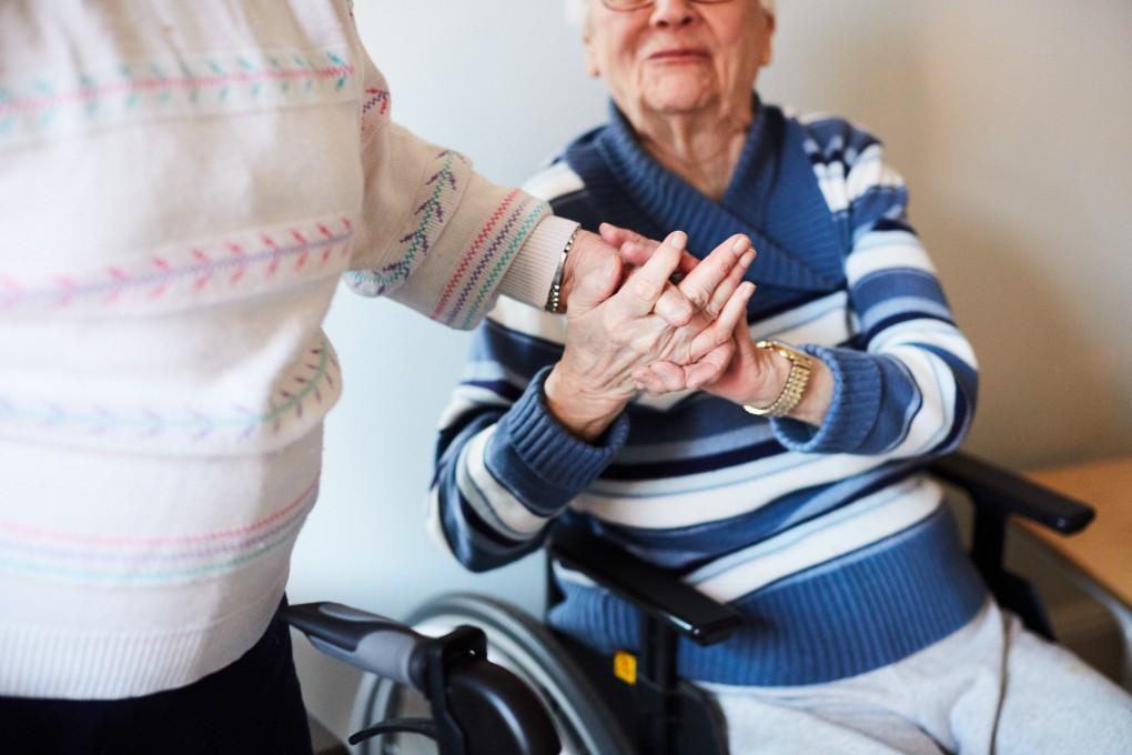 Två äldra kvinnor tar varandra i handen efter att ha avslutat ett gympass