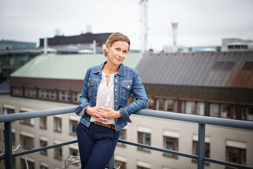 Avslappnat porträtt av medarbetare på AMF Fastigheter med utsikt över Stockholm city